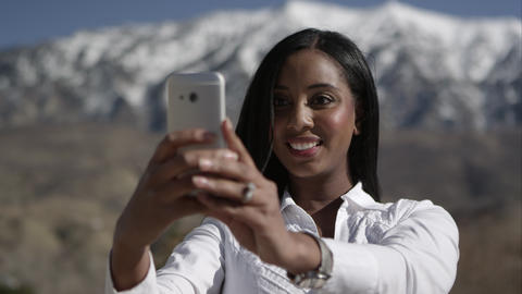 Woman holding smartphone getting ready to take picture of herself Footage
