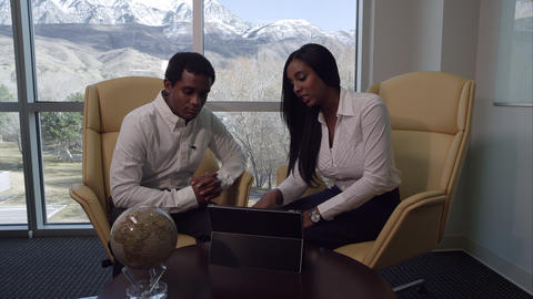 Man and woman having meeting in office by windows Footage
