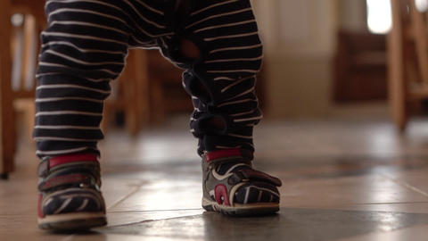 Small baby walks on the citchen in slow motion. Hands and foots in slow motion Footage