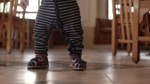 Small baby walks on the citchen in slow motion. Hands and foots in slow motion Live Action