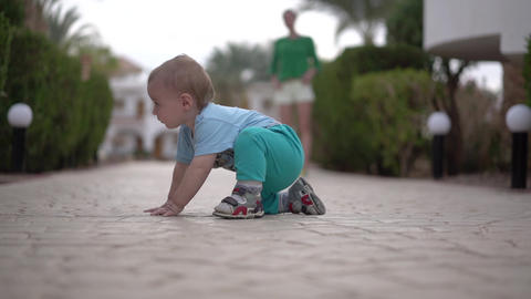 The baby is sitting on the pavement and looking under the bush - funny action Footage