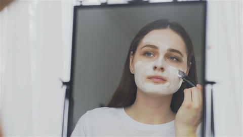 Woman putting facial mask on her face in front of the mirror Live Action