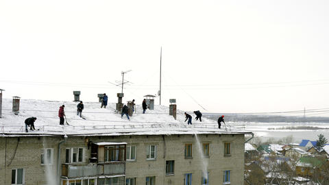 Many men throw white snow from the roof of a multi-storey building Archivo