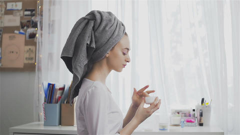 Beautiful healthy woman in a towel putting moisturizing cream on face Live Action