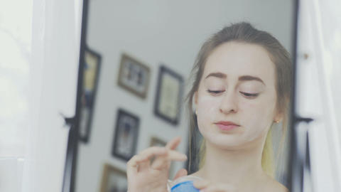 Portrait of a woman with cream or cosmetic mask on her face Live Action
