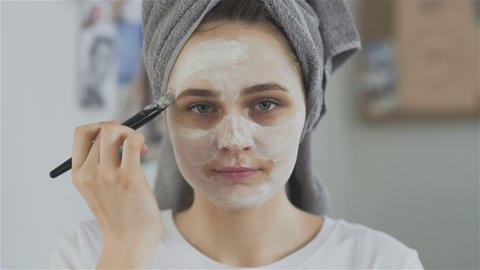 Woman with towel on head applying cosmetic mask and look at the camera Live Action
