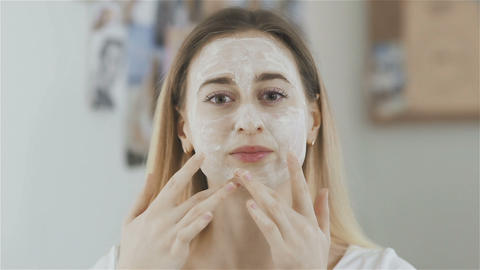 Woman applying cosmetic mask in the room and look at the camera Live Action