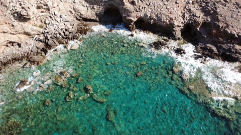 Aerial view of a cave with crystal clear waves at a rocky coast with clear blue Live Action