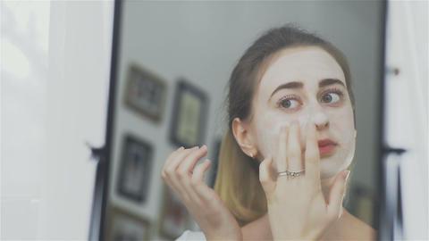 Woman applying mask moisturizing skin cream on face Live Action