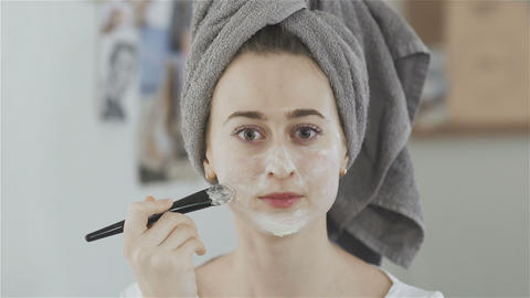 Beautiful woman with towel on head use brush to applying cosmetic mask Live Action
