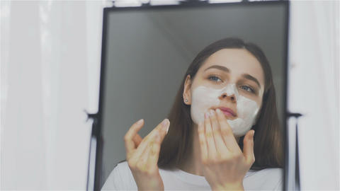 Woman applying mask moisturizing skin cream on face looking in mirror Live Action