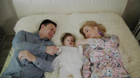 Mother's day. Young cute cheerful family is hugginh in the bed. Mom, dad and Footage