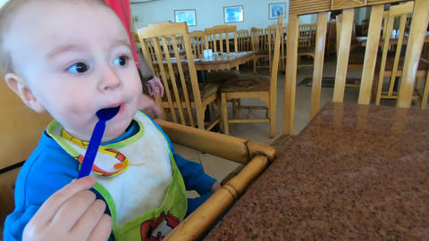 Little baby licks the spoon in the highchair in slow motion GIF