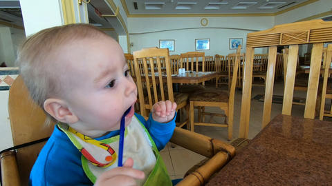 A small child nibbles a spoon in the chair Live Action