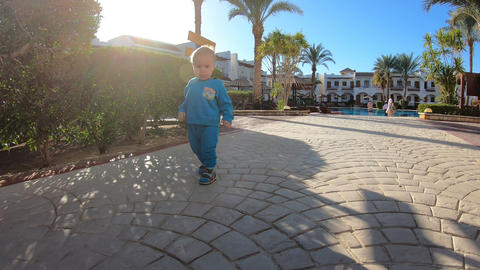 A small child walks around the territory of a tropical hotel in slow motion Footage