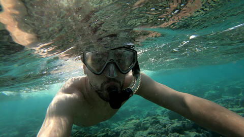 A young guy dives in a mask under the water and swims over shallow water Footage