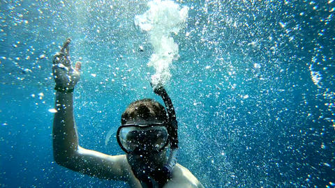 A young guy dives in a mask under the water, magical abstract aqua background Live Action