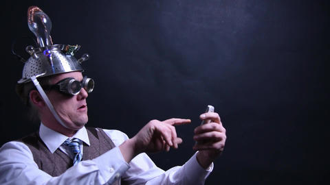 Nerd with aluminum hat is typing on his cellphone Footage