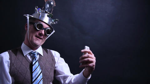 Nerd with aluminum hat looks in love with his cell phone Footage