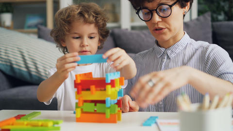 Young woman and her small child playing with wooden construction blocks at home Archivo