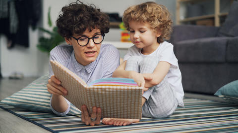 Adorable child boy is listening to fairy-tale while mom is reading story at home Footage