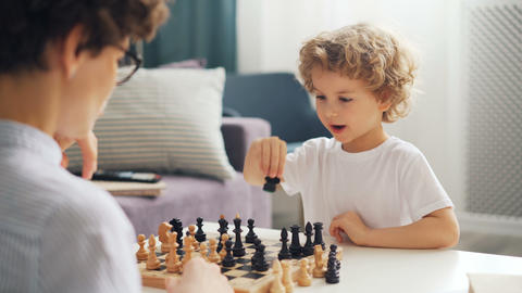 Emotional young kid playing chess with mommy moving pieces on board and smiling Footage