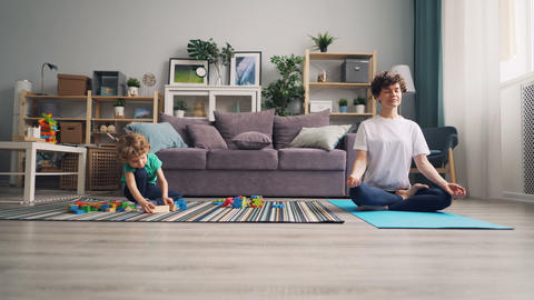 Mom relaxing in lotus position while calm child playing with toys wooden blocks Footage