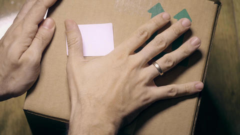 Man sticks a white sticker label to parcel carton box. Place for revealing text Footage