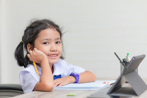 Asian little girl in student uniform doing homework and using ta フォト