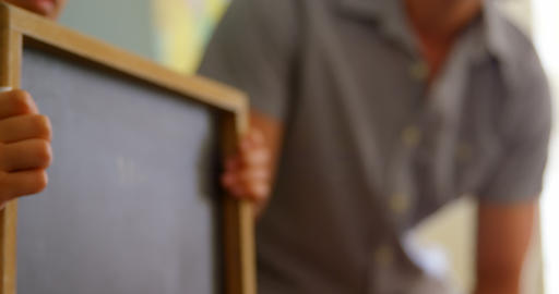 Schoolboy standing with chalk slate in classroom at school 4k Live Action
