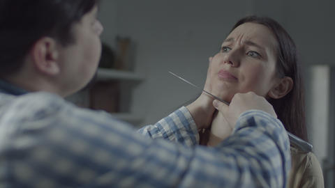 Woman being afraid to move with knife at throat Live Action