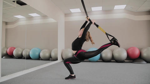 In an afro training woman does exercises on suspended TRX belts in gym. Strong Footage