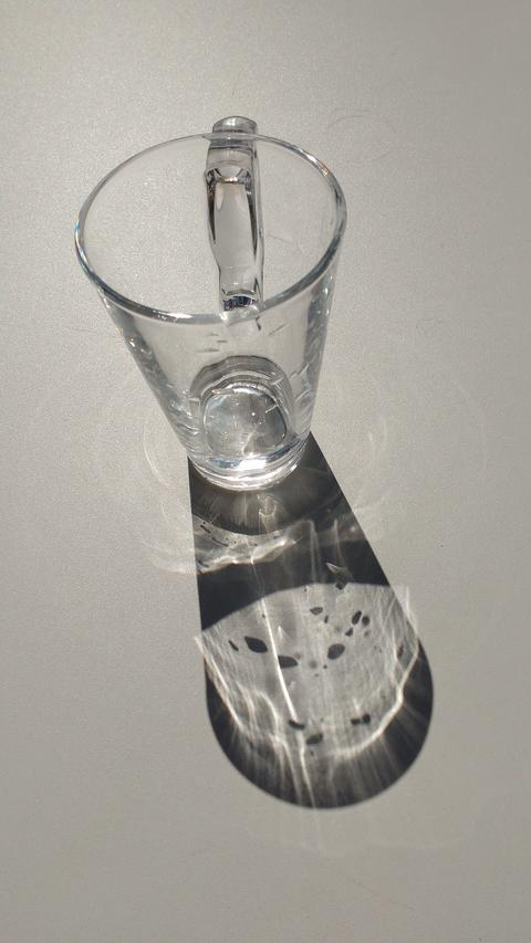 Clear, Empty Glass of Water on Table in Sun with Shadow フォト