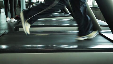 Close up of running male legs on treadmill GIF