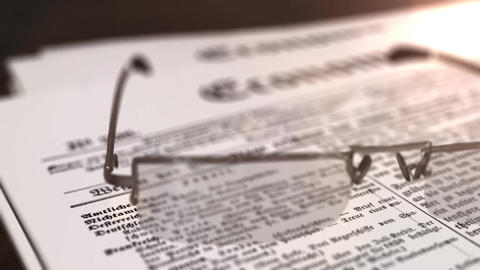 glasses with newspaper with the headline Economy on a table Animation