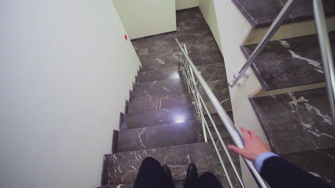 businessman walks down marble stairs view from headcam Footage