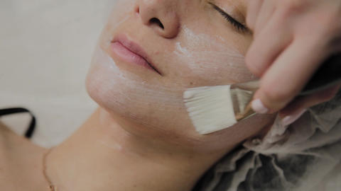 Skilled cosmetologist puts mask on face of lying woman in spa salon indoors Footage