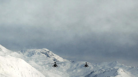 Apache Helicopters In Snowy Mountains stock footage