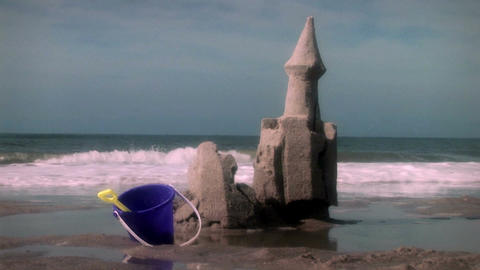 1003 Crumbling Beach Sand Castle Ocean Waves and Toys Stock Video Footage