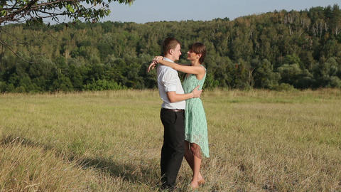 Young couple hugging on the yellow grass Stock Video Footage