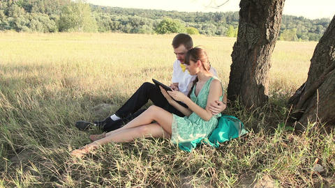 Young couple browsing in Internet with tablet and chating Footage