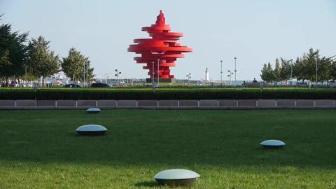 Red torch sculpture,Green grass & Seaside... Stock Video Footage