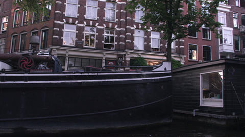 Sped-up video of buildings on a street and houseboats along the canal in Amsterd Footage