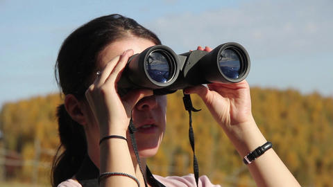 Woman looks through binoculars at the landscape around the lookout point 03 Footage