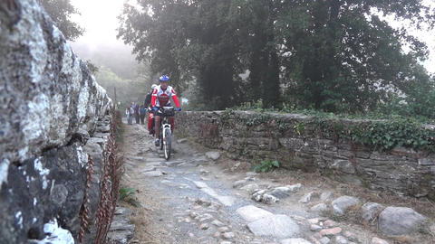 Group of cyclists and walkers pilgrims crossing the over an old stone bridge 02 Footage