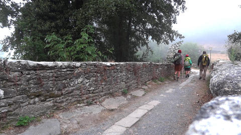 Group of tourists with luggage behind crossing the an old stone bridge next to a Footage