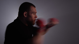 Static shot of man in black shirt and red straps shadow boxing with lens flare Footage
