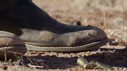 Up close view of cowboy boots as bullet shells fall to the ground next to them Footage