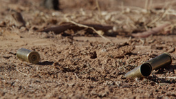 Up close view of bullet shells hitting the ground Footage