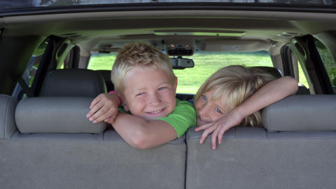 View from back of vehicle looking at kids peaking over the back seat Footage